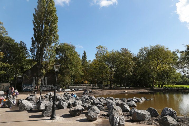 "Oosterpark 26/09/2015 13h07 In the year 2015 the Oosterpark has undergone a renovation. Lots of trees were cut and some footpaths were shifted and relocated. And the park has been extended at the Northwest part along the 's-Gravensandestraat (the garden of Hotel Arena). The playground and tennis court has gone and is replaced by a pond with boulders and fun fountains. This photo is taken on the opening day of the park. Oosterpark The Oosterpark in Amsterdam is the first large park laid out by the municipality of Amsterdam. The park is located in the Oost/Watergraafsmeer borough and forms a component of the Oosterpark area. The park, an English garden, was designed by Dutch landscape architect Leonard Anthony Springer and was laid out in 1891. In order to create the Oosterpark, a centuries old cemetery behind the Tropical Museum had to be relocated. There were a lot of protests at the time when the municipality of Amsterdam suggested the new plans. In the end the protesters gave in and agreed with the new location for ""their"" cemetery which is now known as the New Ooster Begraafplaats. In the park is a pond with a small island. The park also contains a part of the former cemetery. The park contains The National Slavery Monument, which commemorates the abolition of slavery in the Netherlands in 1863. The monument was unveiled on July 1, 2002 in the presence of Her Majesty Queen Beatrix. The dynamic dimension of the monument, the National Institute for Dutch Slavery and its Legacy (NiNsee) was opened on July 1, 2003. Every year on July 1, NiNsee commemorates the abolition of Dutch Slavery in the Oosterpark with the Keti Koti festival. The Oosterpark also contains a memorial to Theo van Gogh, a film maker and controversial columnist who in 2004 was murdered nearby by a Muslim extremist. Along the park towards Linnaeusstraat (close to the Royal Tropical Institute) there are a number of grey heron nests. The streets lining the southern and western borders"
